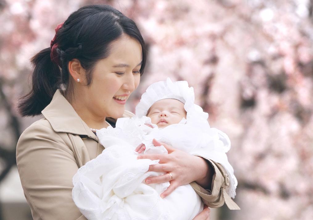 桜の前でお宮参りの写真
